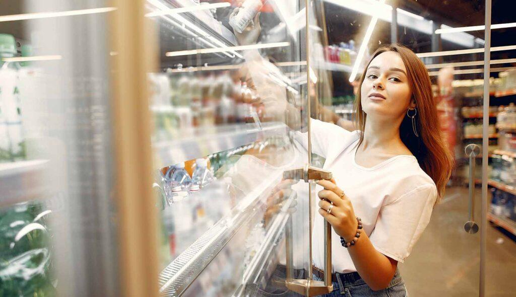 スーパーマーケットで食材を選ぶ母親