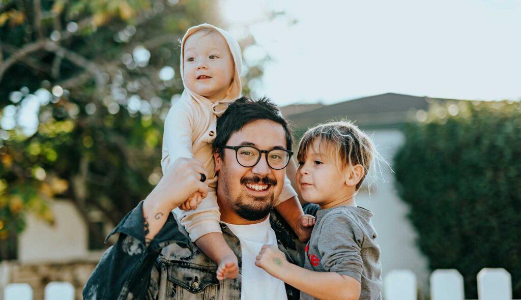 二人の子供を抱きかかえるシングルファザー