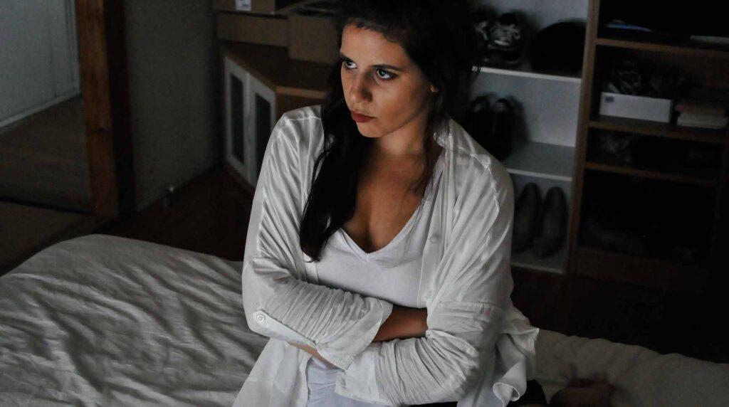 暗い室内で腕を組みムカついた表情の女性の写真
