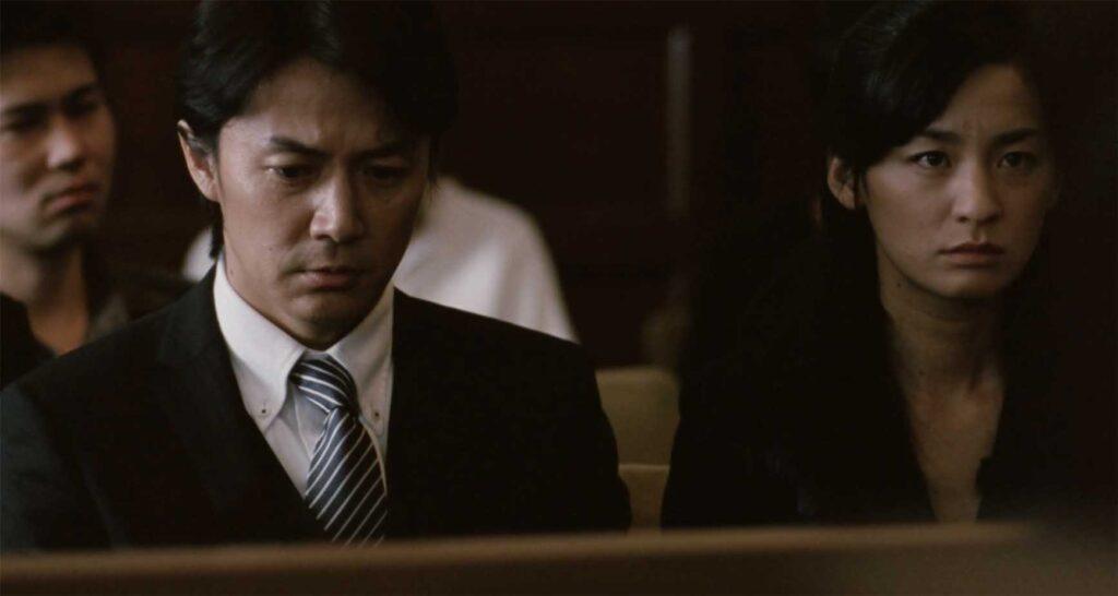 裁判所の傍聴席の《家族A》夫婦