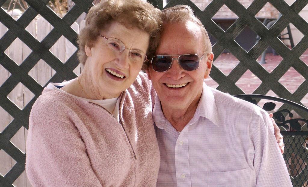 ピンクの服を着て肩を抱き幸せそうに微笑む老夫婦