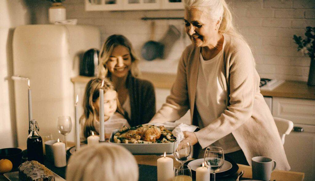 豪勢な手料理を振る舞う祖母と、横で微笑む母、その膝に座る娘