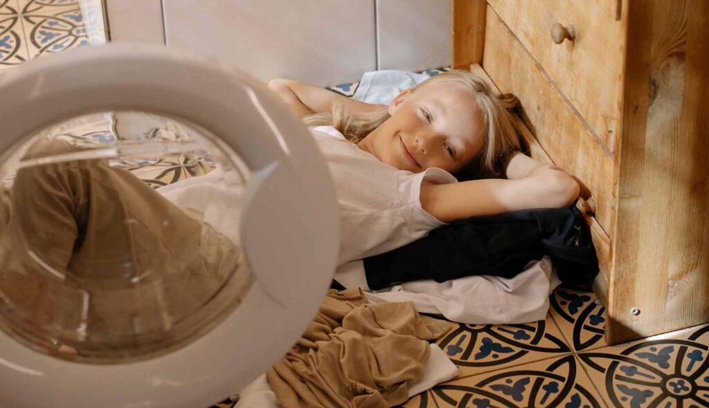 洗濯物の山の上で優雅に寝転ぶ少女