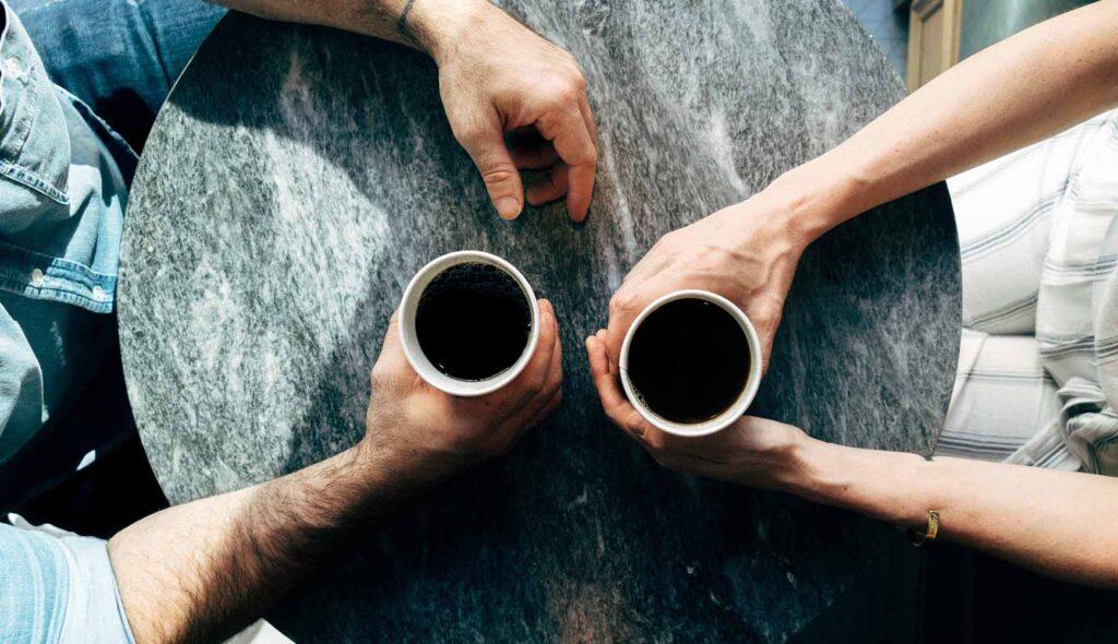 コーヒーカップを手に向かい合って話し合うカップル