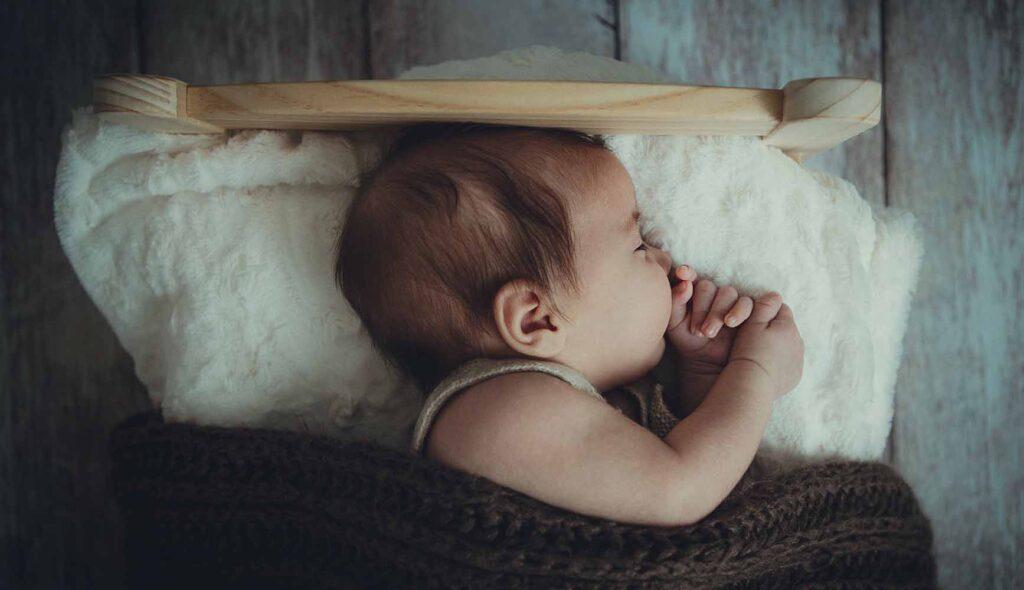 ベッドで指をくわえて眠る赤ちゃん