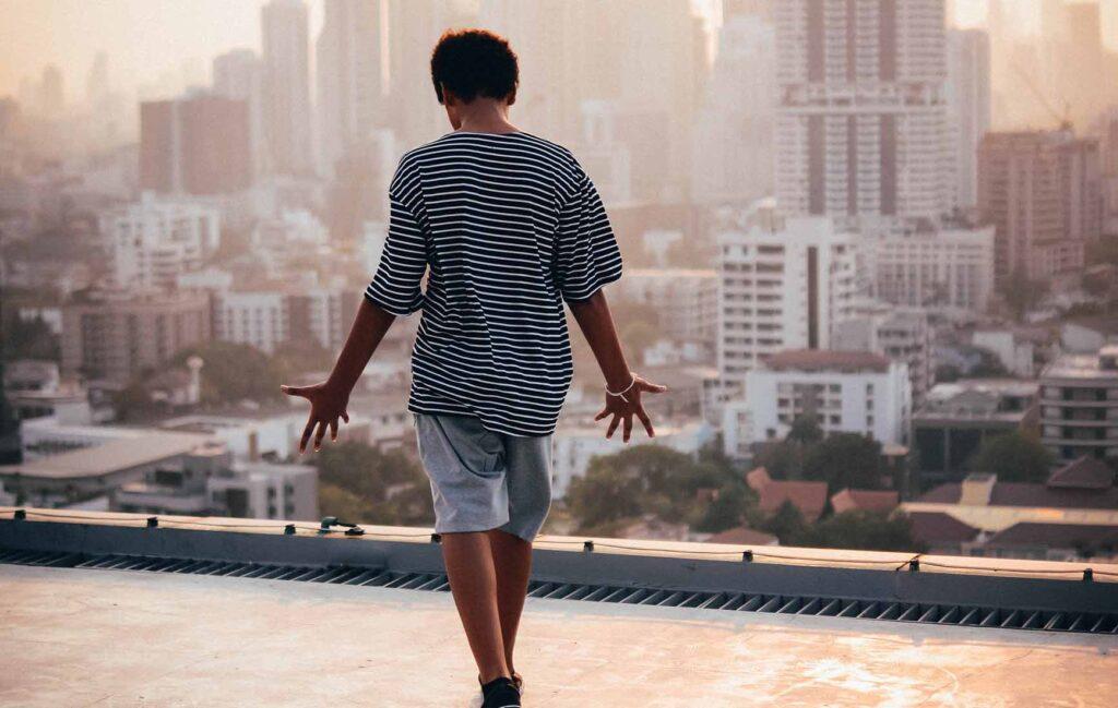 朝日に浮かぶバンコクのビル群を前に、手を広げる若い男性