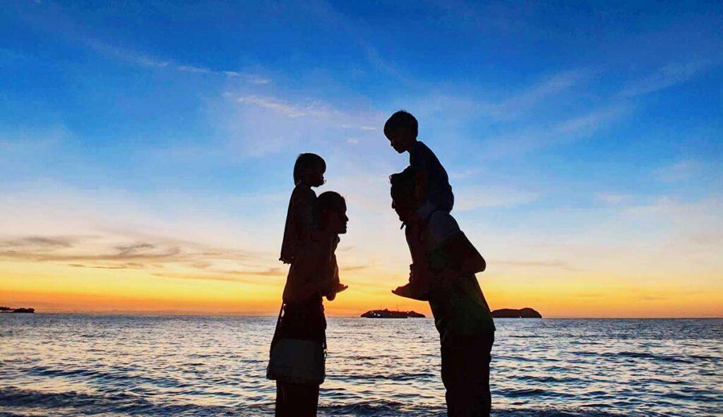 海辺で子供を肩車して向かい合う男女のシルエット