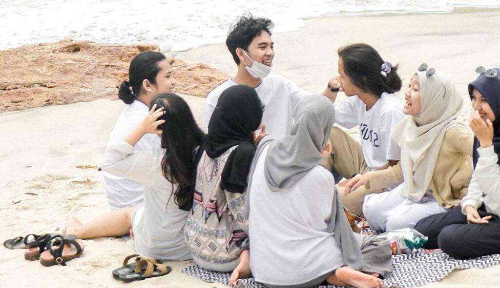 男性を取り囲みピクニックをする複数の女性
